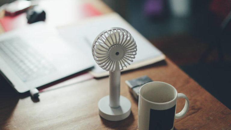 Schreiben bei Hitze. Ventilator und Becher auf Schreibtisch. Photo by Siniz Kim on Unsplash