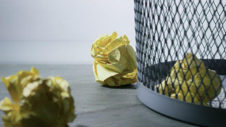 Bye bye Überforderung - Text überarbeiten ohne Stress. Zusammengeknülltes Papier in und neben Papierkorb. Photo by Steve Johnson on Unsplash