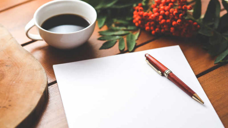 Warum schreiben sinnvoll ist - obwohl es sich nicht so anfühlt. Ein leerer Block und darauf ein edler Füller liegen auf einem hellen Holztisch. Daneben steht eine weiße Kaffeetasse und ein Büschel Ebereschenbeeren. Photo by Kaboompix via Pexels.